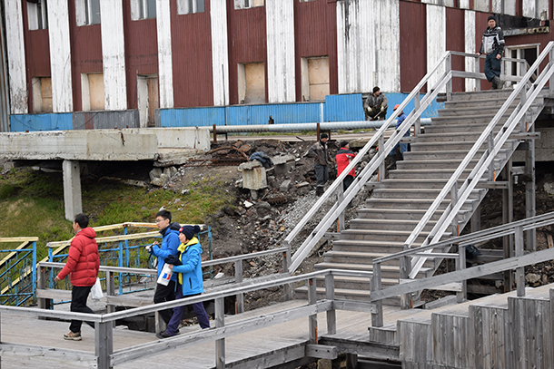 Workers repairing the stairs and tourist walking by. Barentsburg, Norway